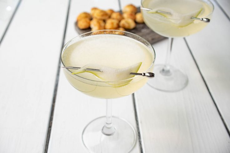Pear Ginger Champagne Cocktail in a coupe glass with a pear slice on a drink skewer
