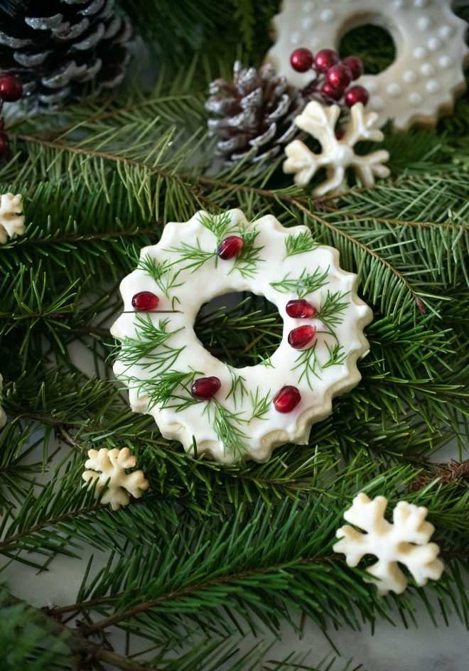 Christmas wreath and snowflake cookies on pine fern with pine cones