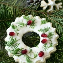 A cookie that looks like a Christmas wreath decorated with white frosting, green leaves and pomegranate seeds on fern