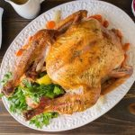 An overhead image of a roast turkey on a white platter with stuffing, mash and cranberry sauce