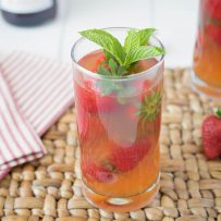 A tall glass of Pimm's strawberry mint cocktail garnished with fresh strawberries and mint