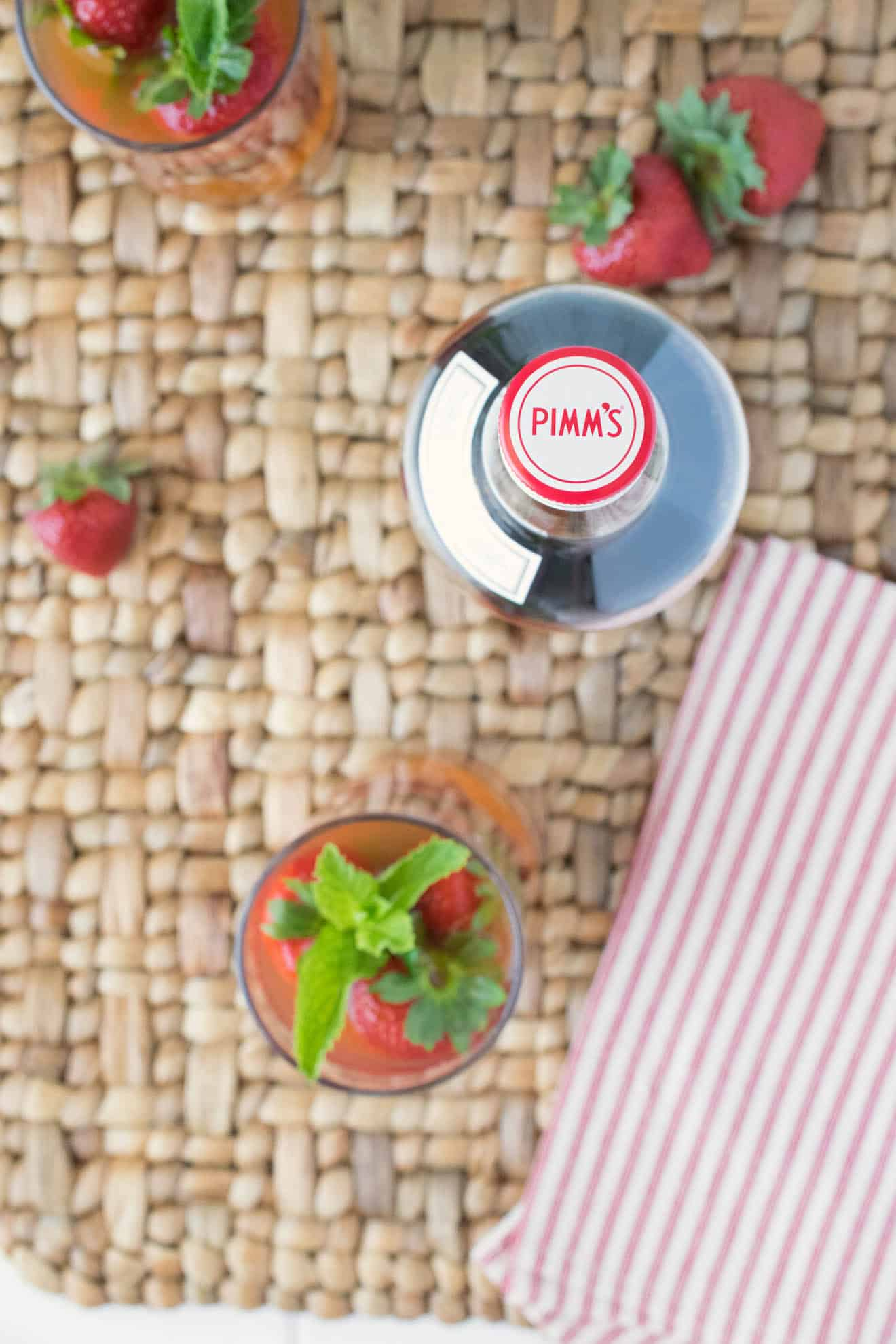 A view from overhead of the Pimm's bottle and drink with fresh strawberries and a striped napkin