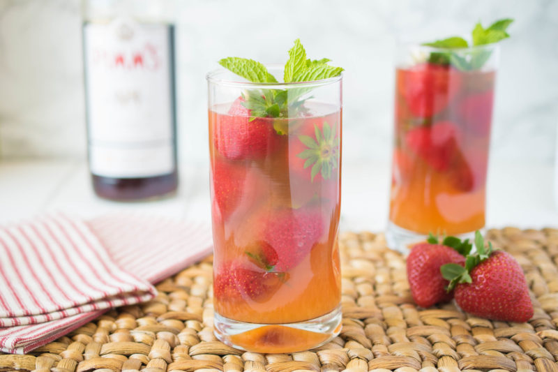 A tall glass with whole strawberries