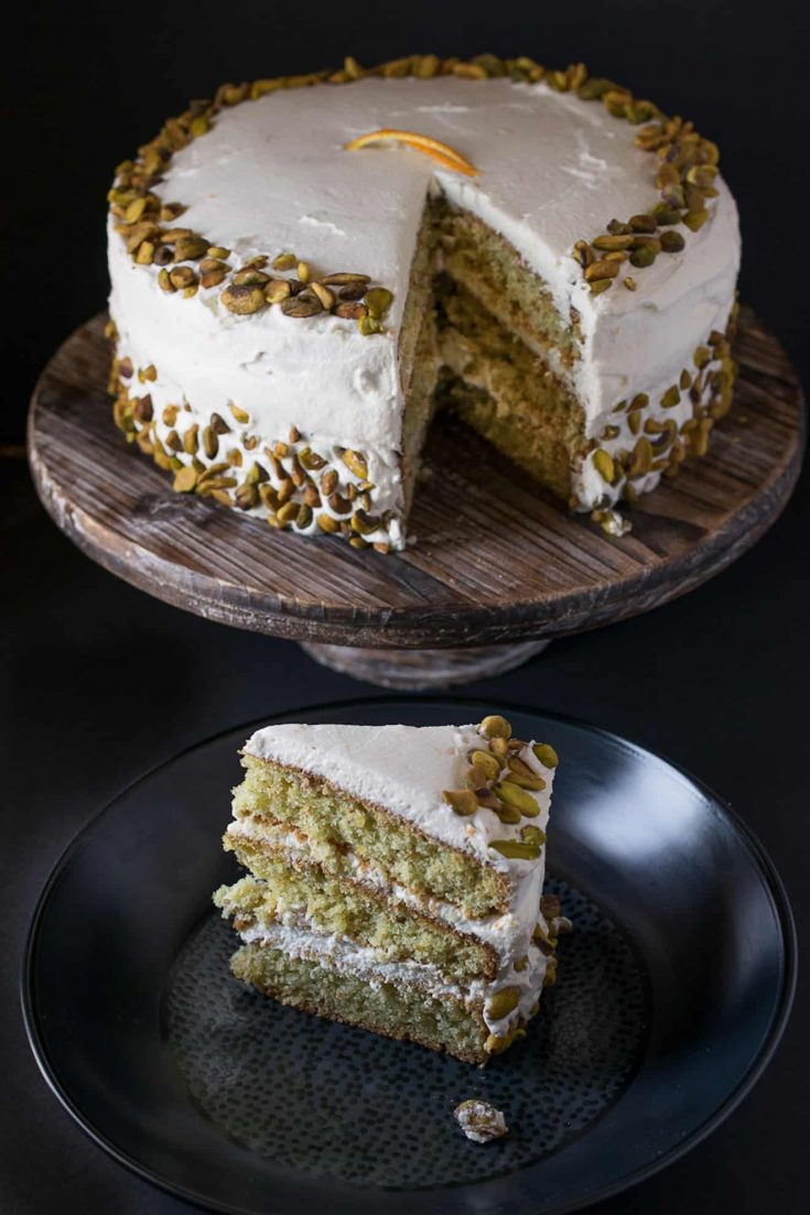 A whole pistachio cake on a wood cakes stand with a slice next to it on a black plate