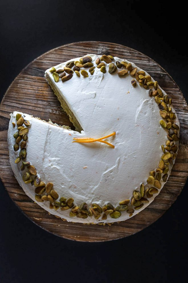 The pistachio cake viewed from overhead with a slice remove and fresh orange garnish
