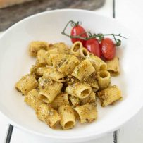 A bowl of pistachio pesto pasta with cherry tomatoes on the vine