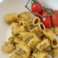 Rigatoni pasta coated in pistachio pesto with cherry tomatoes