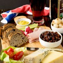 A classic Ploughman's lunch. A board with bread, meats, pickle, cheeses and beer.