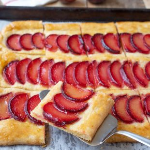 A slice of plum tart on a spatula