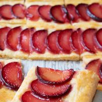 A closeup of a square of plum tart