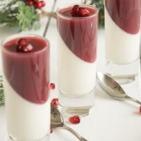 3 small glasses of pomegranate panna cotta with spoons