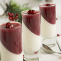 Pomegranate panna cotta decoratively presented in a glass half white and half red