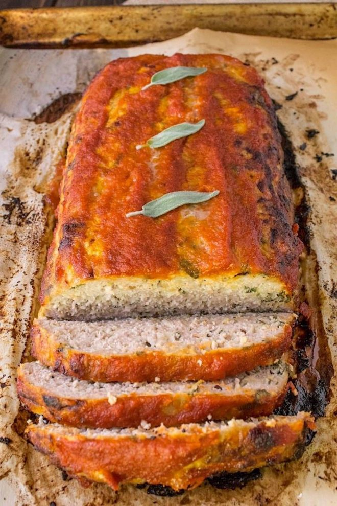 Pork apple and sage meatloaf right out of the oven with fresh sage leaves