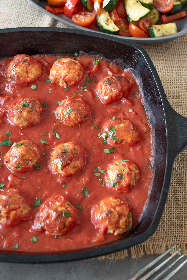 A cast iron skillet filled with meatballs baked in tomato sauce