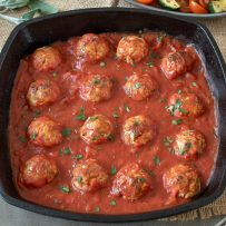 Pork ricotta and sage meatballs bathed in a pan of tomato sauce garnished with fresh parsley