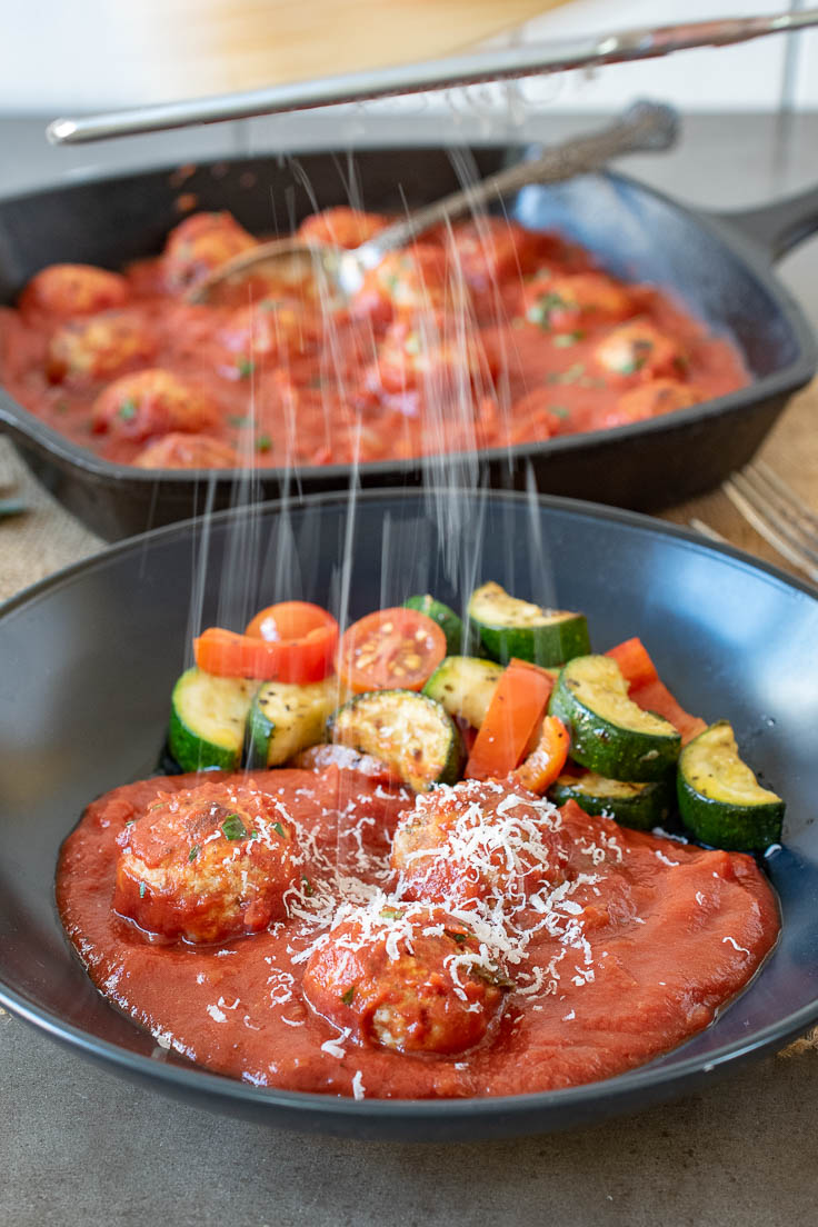 Parmesan cheese being grated over meatballs with zucchini and tomatoes