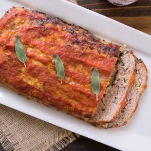 A whole pork apple and sage meatloaf on a long white platter