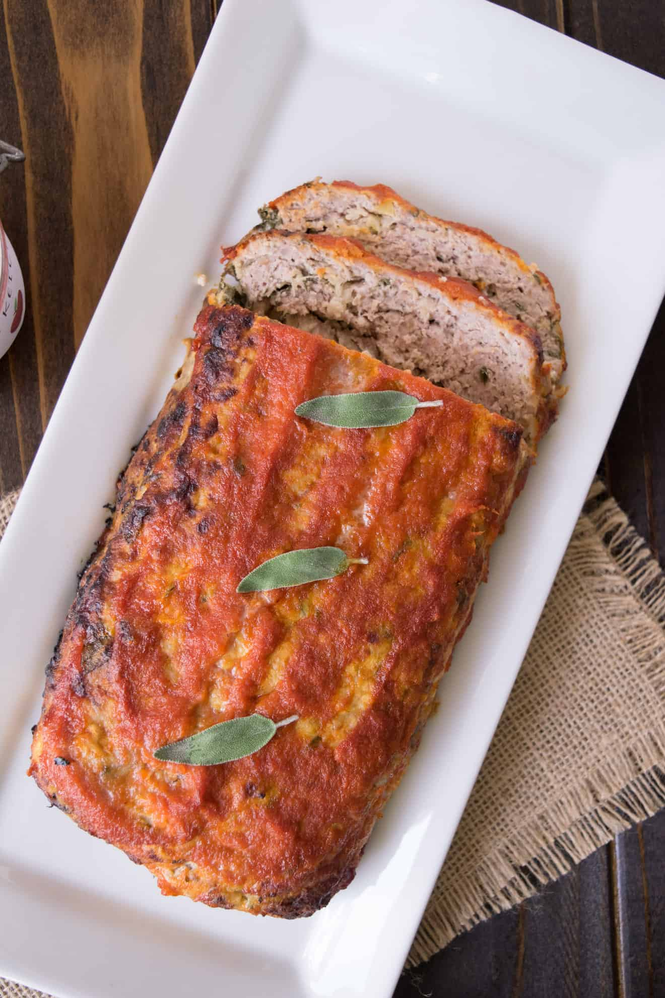 Pork apple and sage meatloaf with some slices on a serving plate
