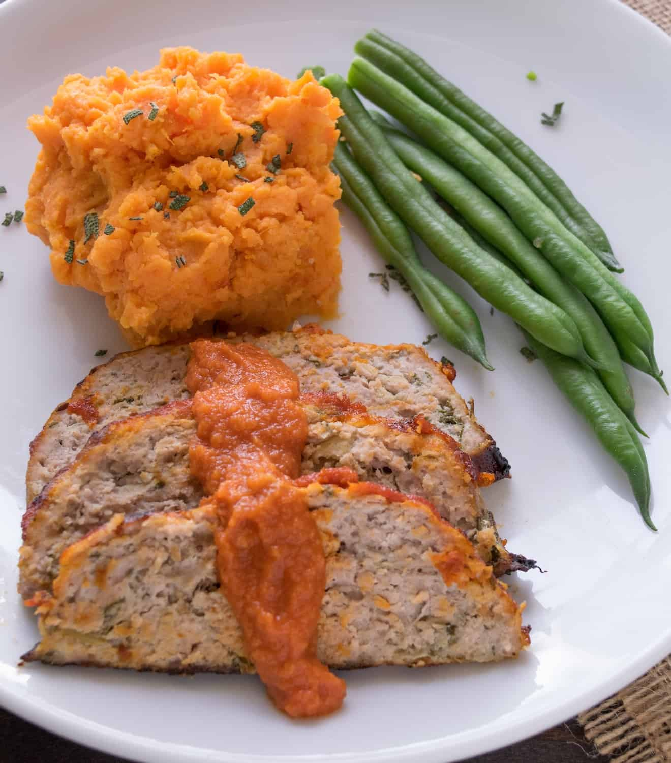 Sliced pork apple and sage meatloaf on a plate with green beans and mash
