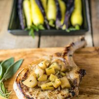 A pork chop on a cutting board topped with chopped apples