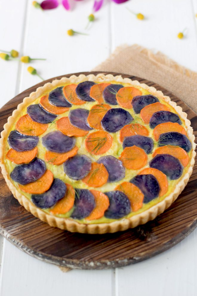 Layers of sliced orange and purple potatoes on top of a quiche