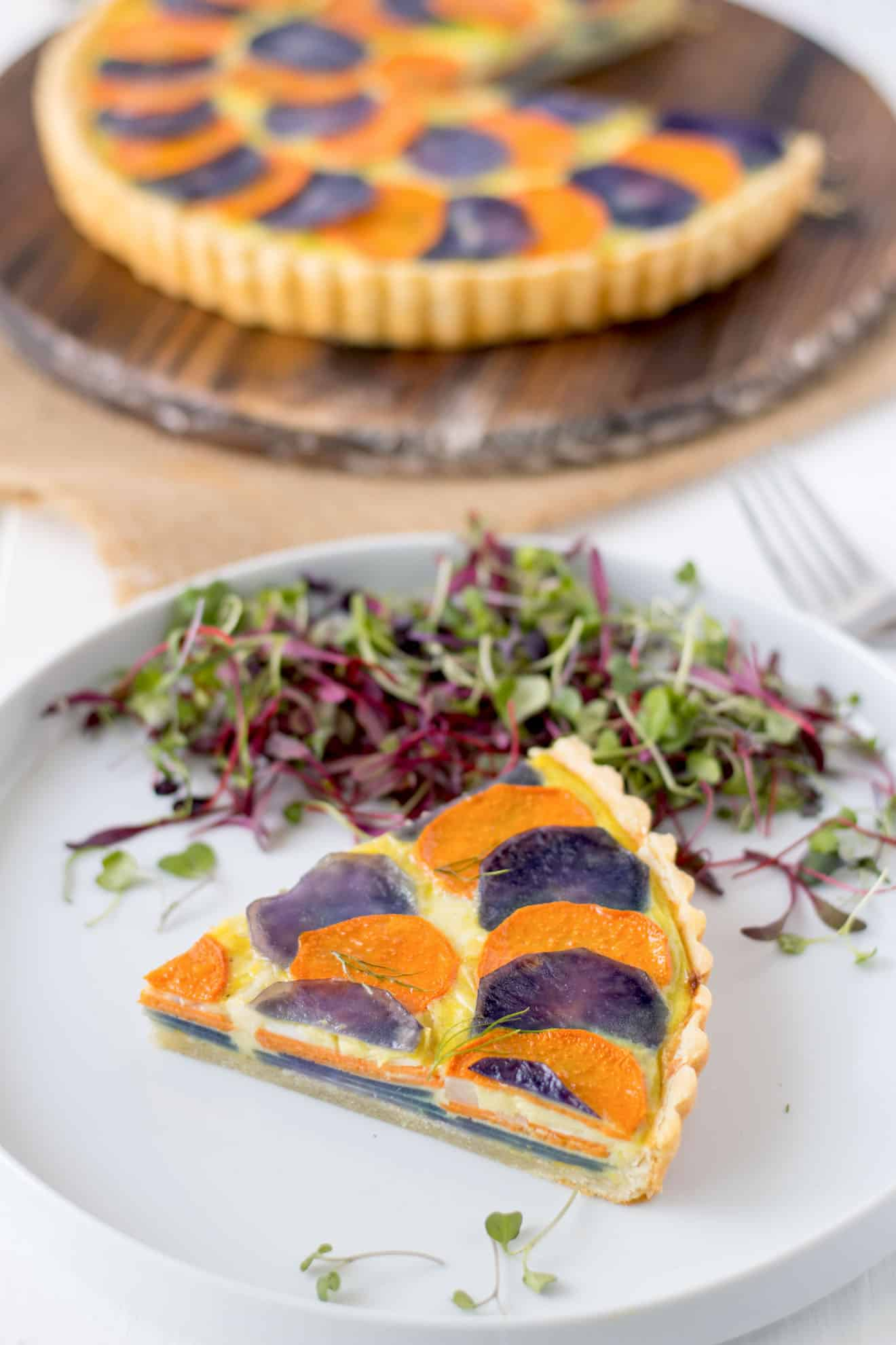 A slice of potato and vegetable quiche on a white plate with micro greens