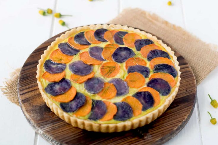 Potato and vegetable quiche topped with slices of orange and purple potatoes