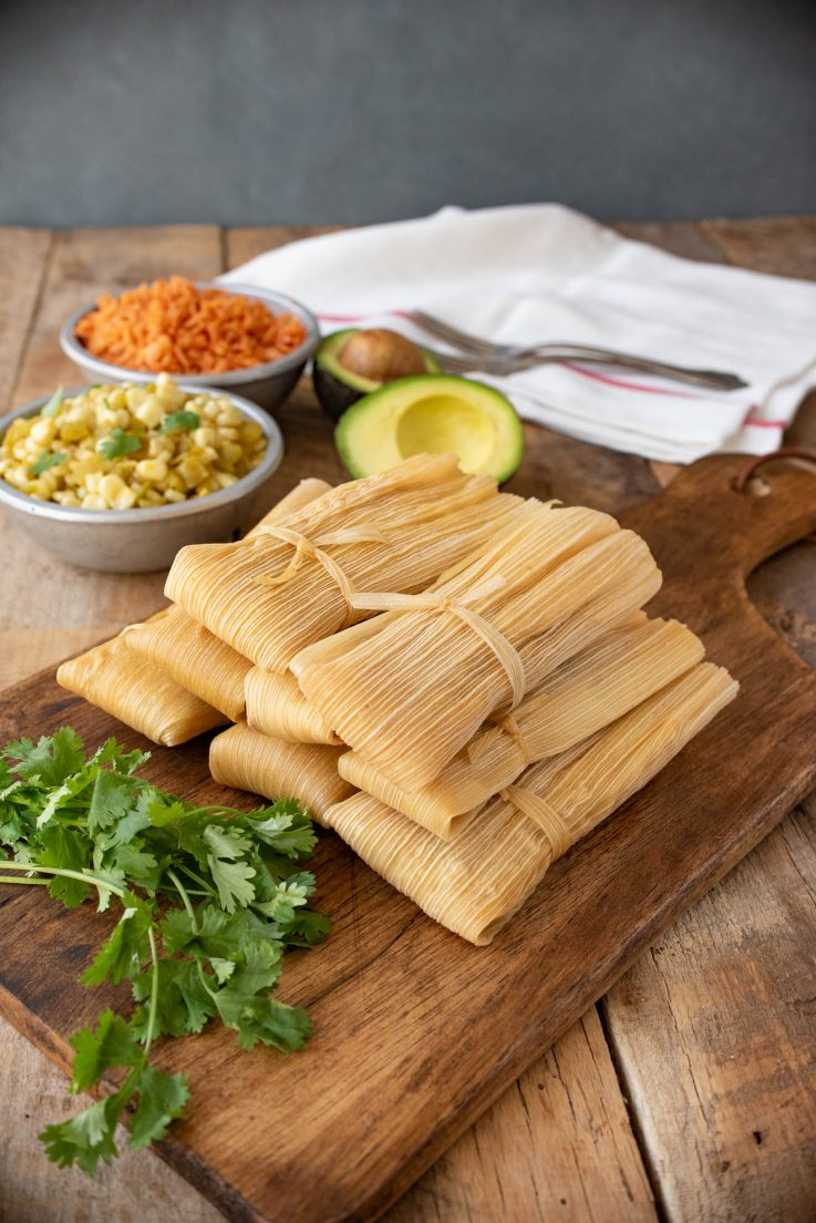 Tamales wrapped in corn husks piled onto a serving board
