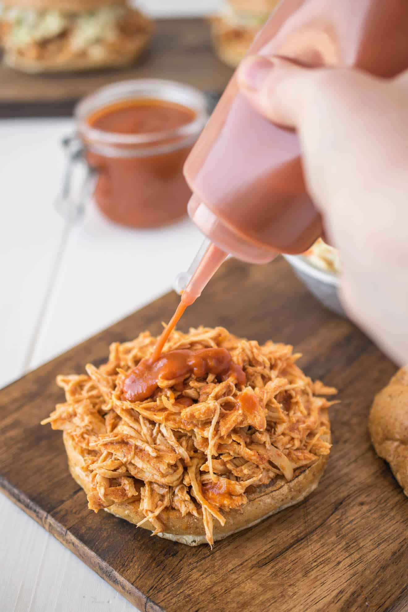 Pouring barbecue sauce on to pulled chicken