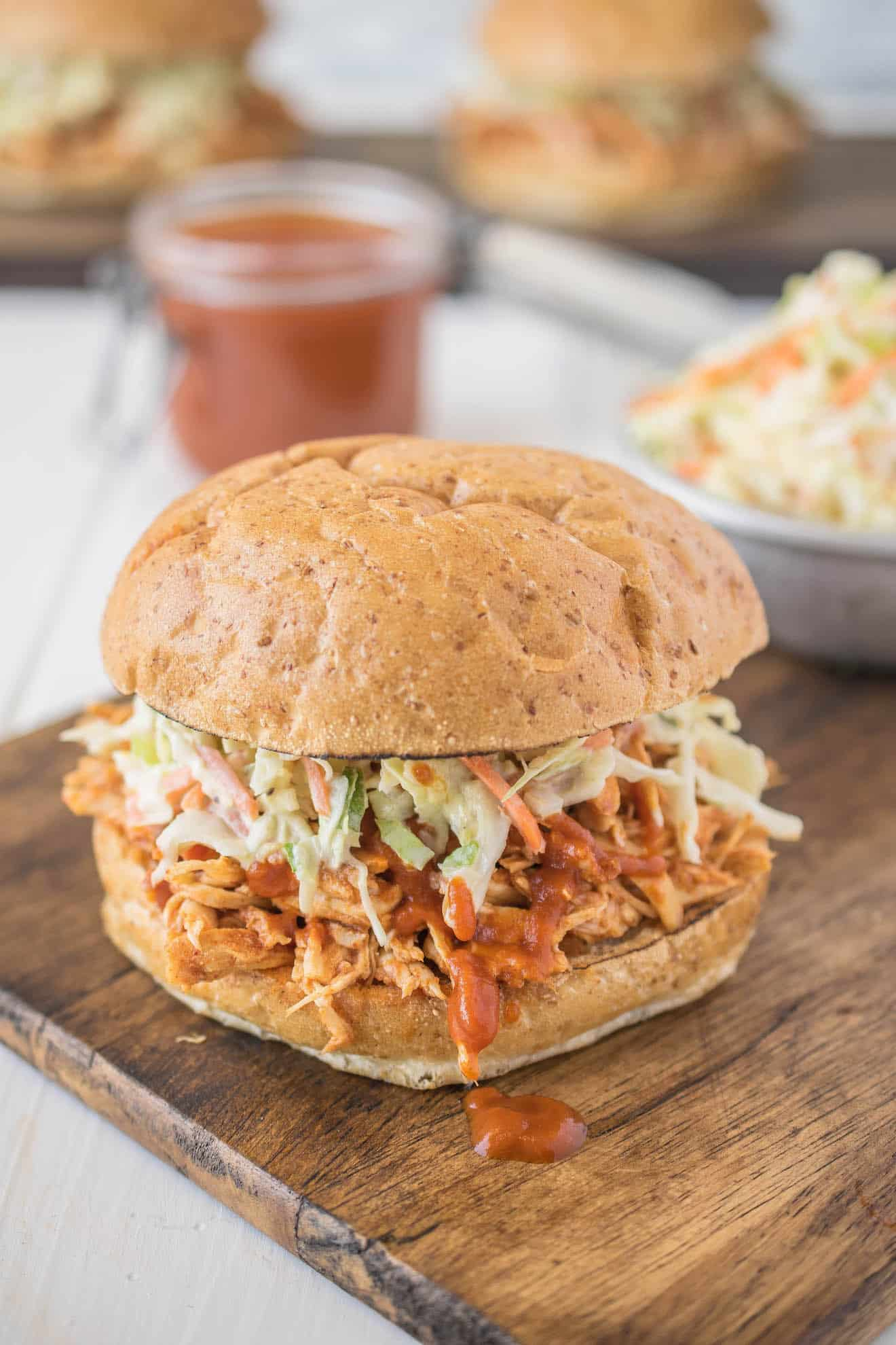 Pulled chicken in a sandwich bun topped with barbecue sauce and coleslaw