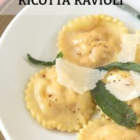 Fluted edge round ravioli on a white plate with crispy sage leaves and shaved Parmesan cheese