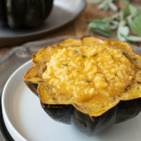 A side view of pumpkin risotto stuffed acorn squash with another in the background