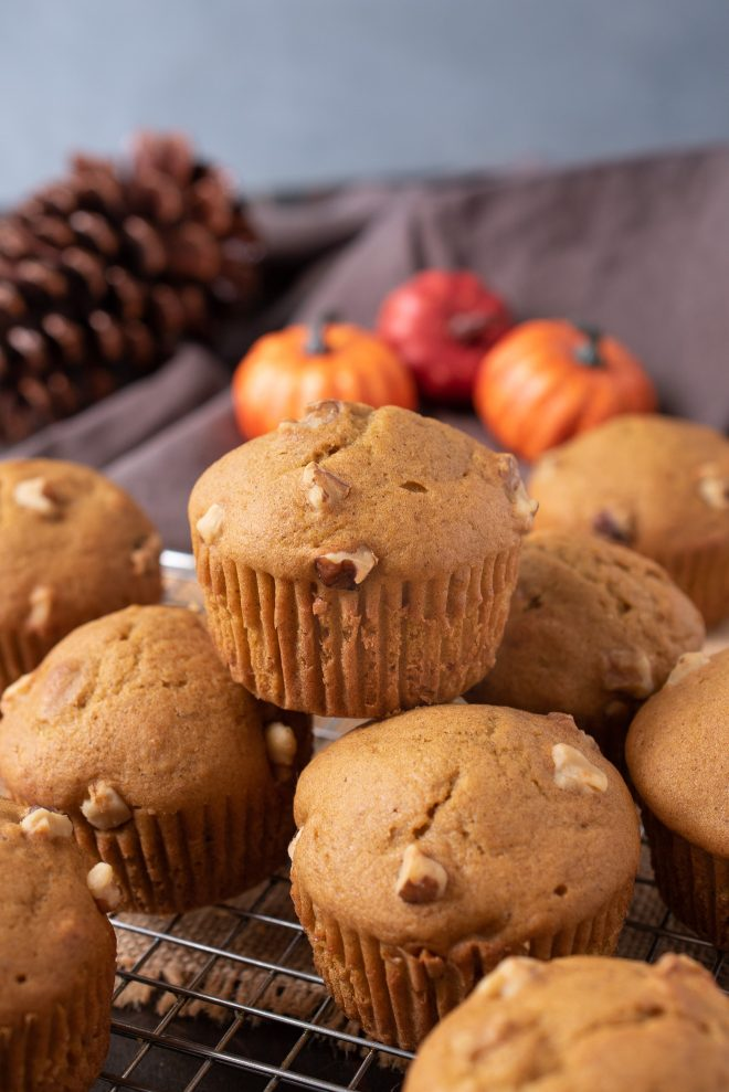 Pumpkin walnut muffins on a rack with 1 on top