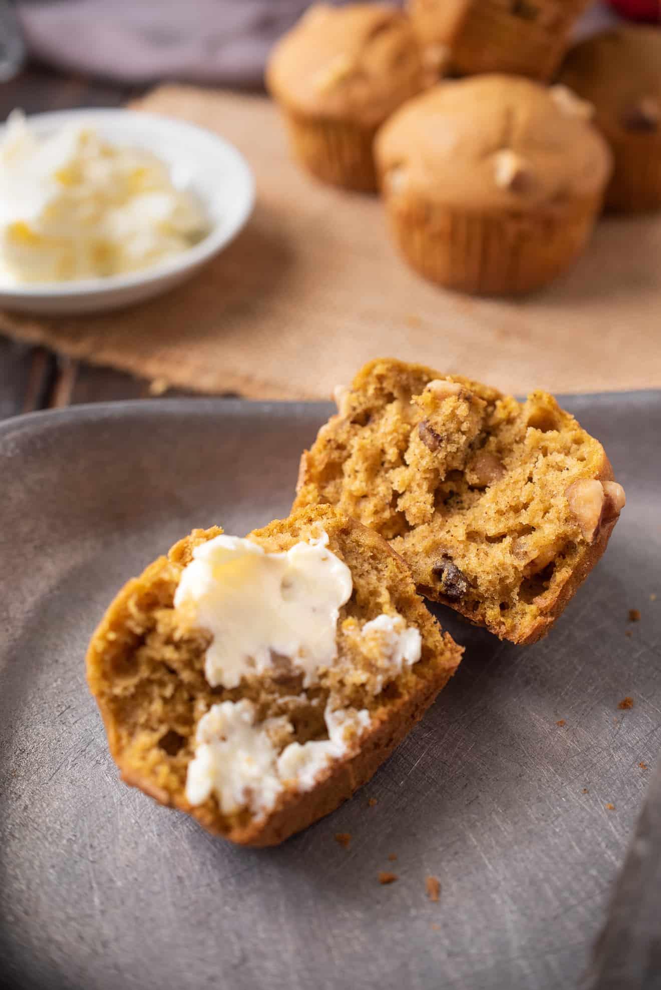 A pumpkin walnut muffin cut in half spread with butter