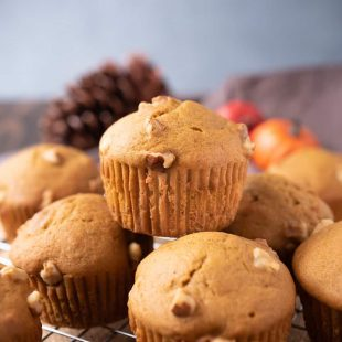 A pumpkin walnut muffin on top of other muffins