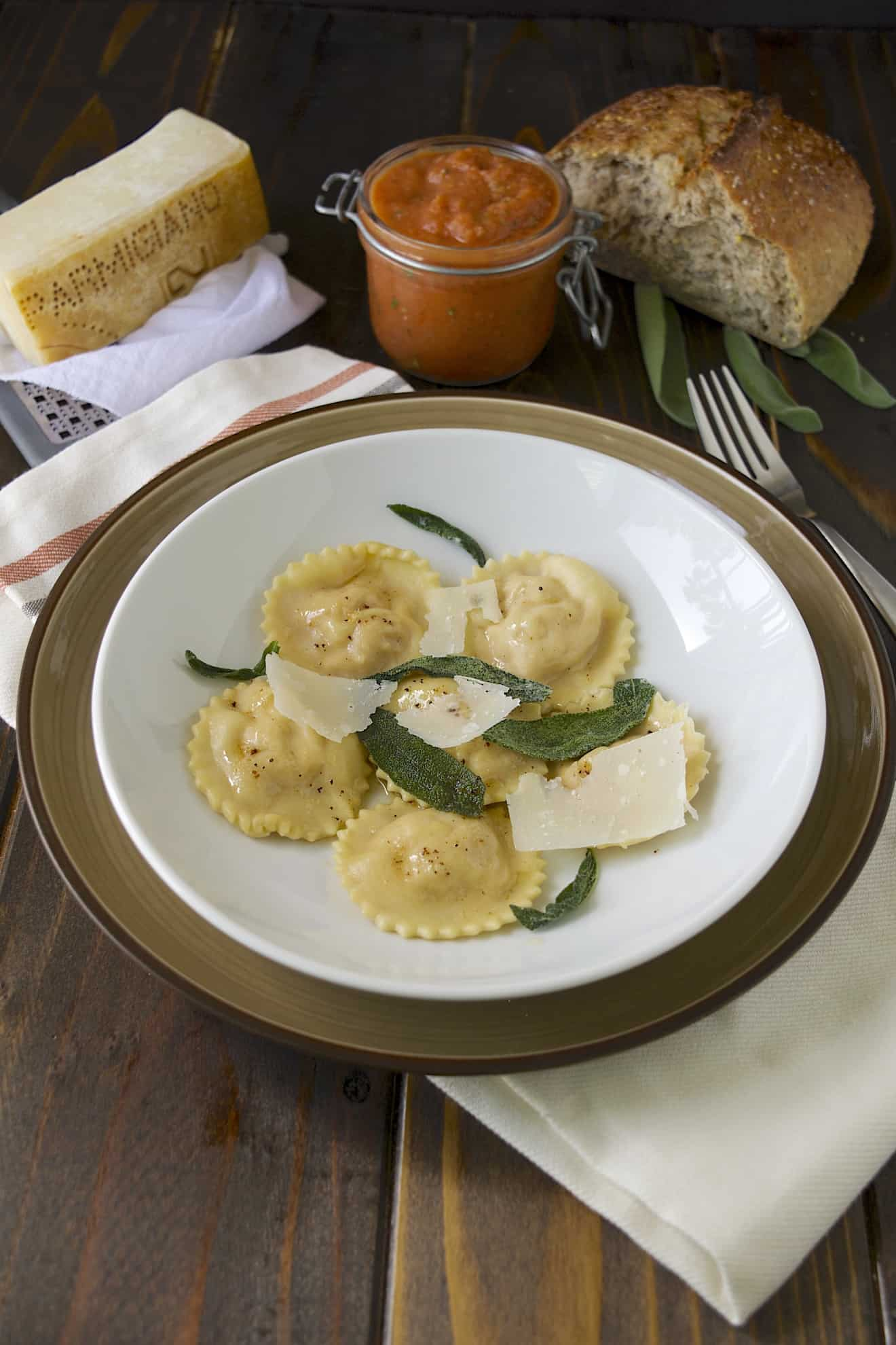 A white bowl of pumpkin ricotta ravioli garnished with sage and cheese and a side of marinara sauce