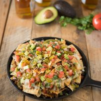 Nachos topped with tomato, jalapeño, avocado and cilantro with bottles of beer in background