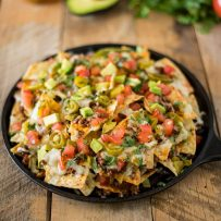 A round pan holding a pile of queso fundido nachos