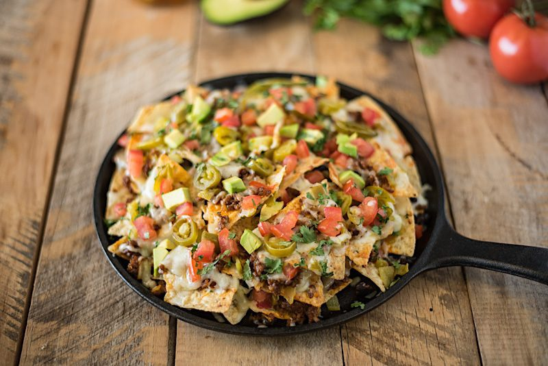 A black cast iron skillet loaded with nachos