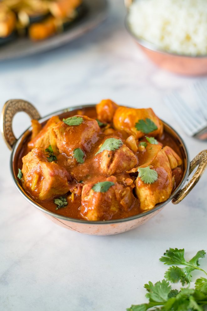 Chicken madras served in an Indian Karahi topped with fresh cilantro