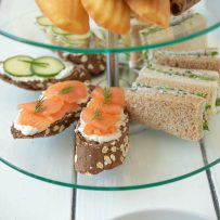 A selection of sandwiches on a tiered tray. Salmon and cream cheese, radish and herb butter