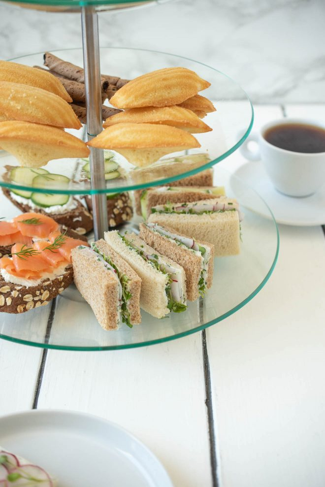 Madeleine cookies and sweet treats in a tiered cake stand with tea sandwiches