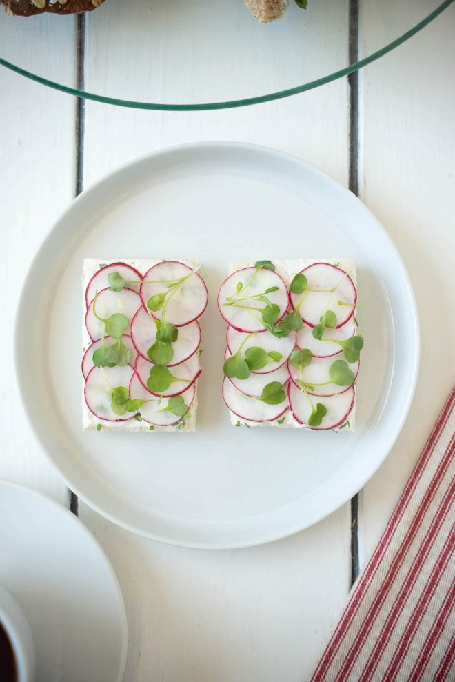 2 open-faced radish and herb butter sandwiches topped with micro greens