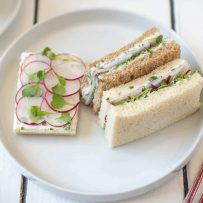 An open faced and mini crustless radish and herb butter sandwiches on a white plate
