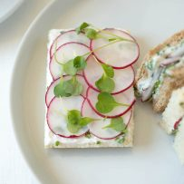 A closeup of an open-faced sandwich with herb butter, sliced radish and micro greens