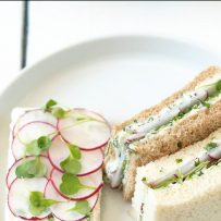 On the left of a plate is an open-faced radish and herb butter sandwich and on the right, 2 crustless sandwiches