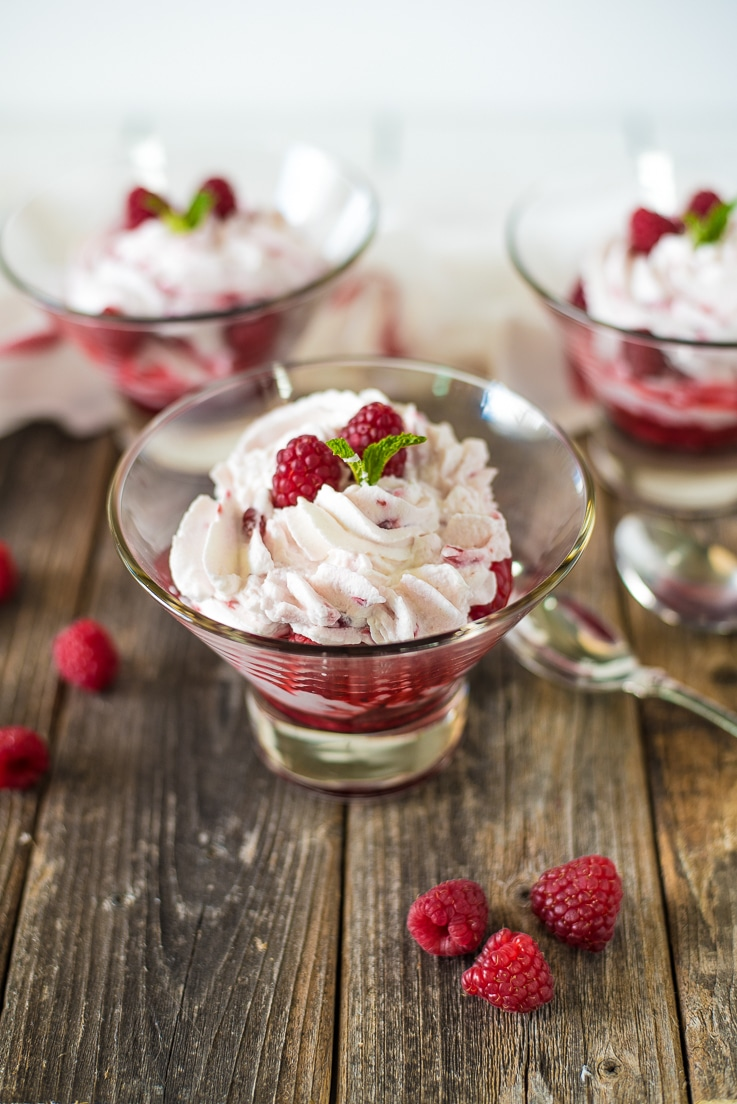 A glass bowl with raspberry fruit fool surrounded by fresh raspberries and spoons