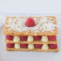 The dessert on a plate showing the red raspberries and lemon custard sandwiched between puff pastry