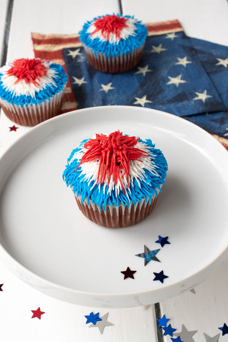 A red velvet cupcake on a white plate with red white and blue frosting