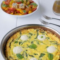 Ricotta and spinach frittata served alongside a tomato salad
